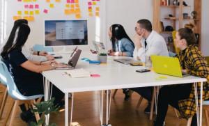 Fünf Menschen sitzen um einen Tisch und schauen gemeinsam auf einen Bildschirm und eine Pinnwand.
