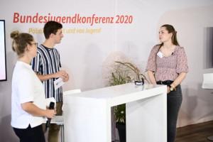 Zwei Frauen und ein Mann diskutieren vor einer Stellwand mit dem Titel Bundesjugendkonferenz 2020, Fotograf Fabian Sommer