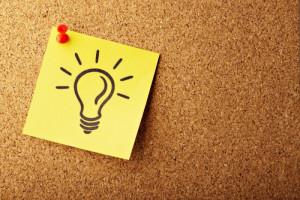 Auf einem Notizzettel, welcher an einer Pinnwand hängt, ist eine Glühbirne gemalt.
