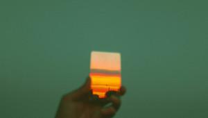 Vor einem grünen Hintergrund hält eine Hand ein Bild von einem Sonnenuntergang hoch.