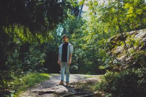 Ein junger Mann steht in einem Wald.
