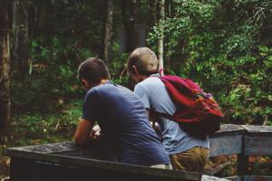 Zwei junge Männer schauen in einen Wald rein.