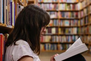Eine Frau sitzt angelehnt an einem Bücherregal und liest ein Buch.
