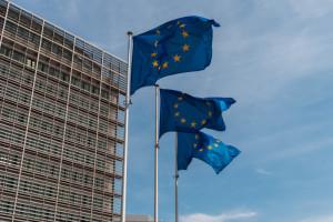 Drei europäische Flaggen vor einem Gebäude.