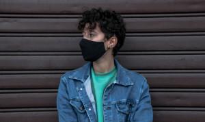 Ein junger Mann trägt eine Mund-Nasen-Maske und steht vor einer Seite und schaut zu seiner rechten Seite.