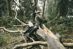 Zwei Frauen sitzen auf einem ungefallenen Baum im Wald.