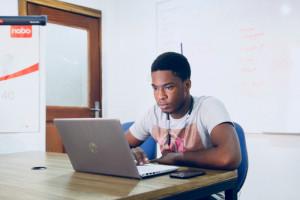 Ein Mann sitzt in einem Seminarraum vor einem Laptop.