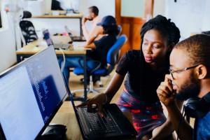 Zwei Menschen stehen vor einem Rechner und reden miteinander.