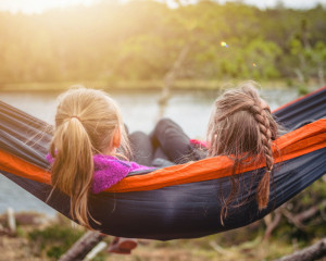 Zwei Mädchen sitzen zusammen in einer Hängematte.