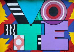 """Das Wort """"Vote"""" ist als Graffiti auf eine Wand gesprüht."""