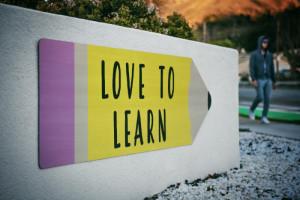 Schild in Form eines Stiftes mit der Aufschrift: Love to learn.