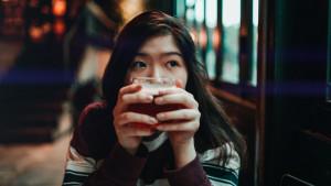 Eine Frau hält ein Getränk in der Hand und schaut zu ihrer linken Seite.